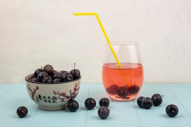 Vista laterale della piccola prugnola di frutta blu-nera acida su una ciotola con un succo su un vetro su un tavolo blu su sfondo bianco