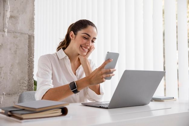 Side view of smiley businesswoman with smartphone and laptop