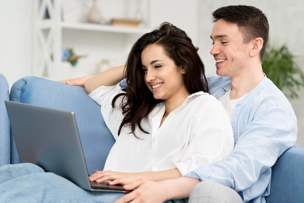 Side view of smiley couple looking at laptop on sofa
