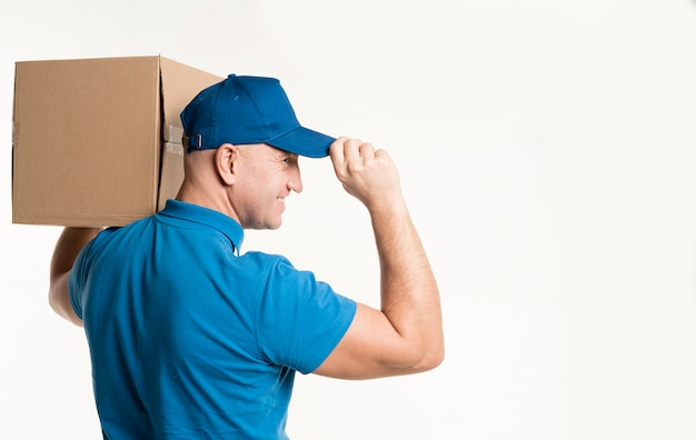 Side view of smiley delivery man carrying cardboard box