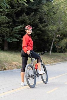 Vista laterale della donna anziana di smiley all'aperto equitazione bicicletta
