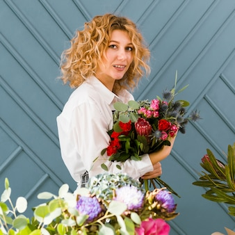Side view smiley florist holding a bouquet of flowers
