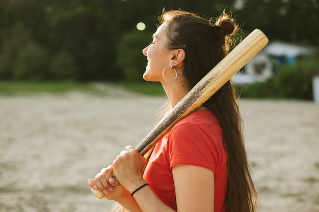 Side view smiley girl holding baseball bat