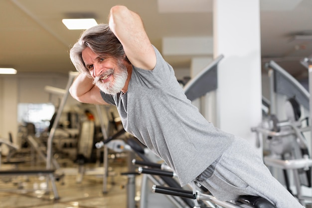 Side view smiley man at gym