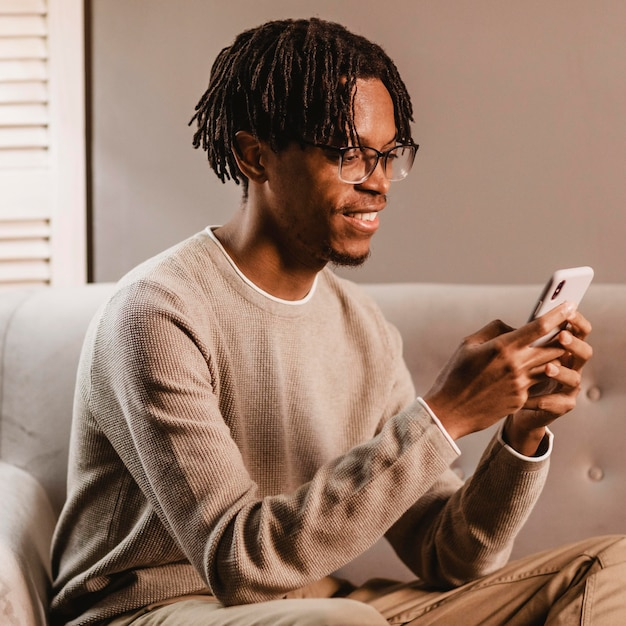 Vista laterale dell'uomo di smiley a casa utilizzando smartphone