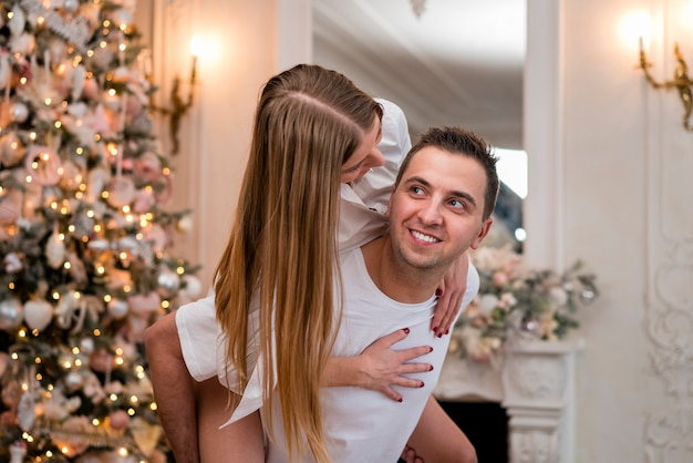 Vista laterale dell'uomo di smiley che trasporta sulle spalle donna