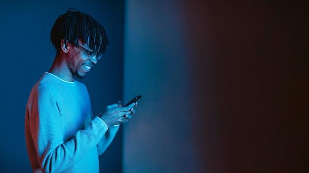 Vista laterale dell'uomo di smiley utilizza lo smartphone con lo spazio della copia