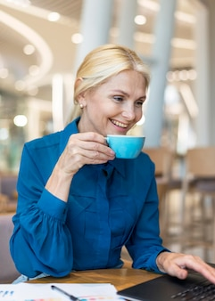 Vista laterale della donna più anziana di affari di smiley che mangia tazza di caffè e che lavora al computer portatile