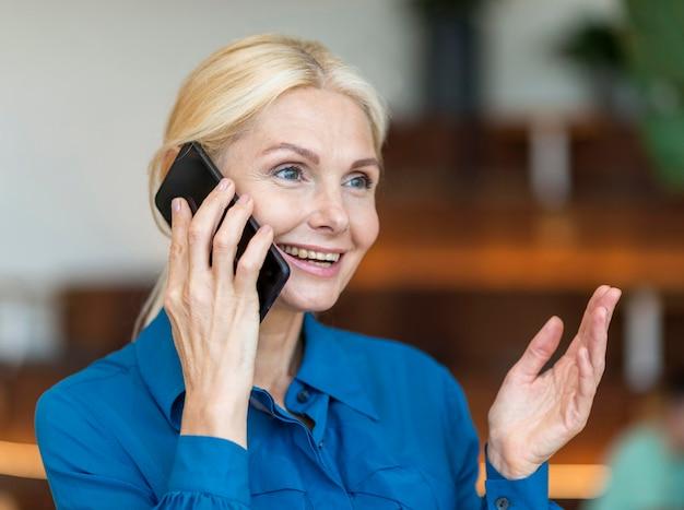 Vista laterale della donna anziana sorridente che parla al telefono mentre si lavora
