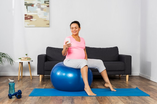 Side view of smiley pregnant woman at home using smartphone and training with ball