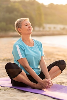 Side view of smiley senior woman doing yoga on the beach