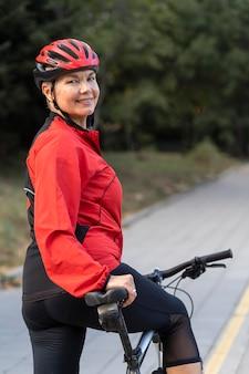 Vista laterale della donna senior di smiley all'aperto equitazione bicicletta