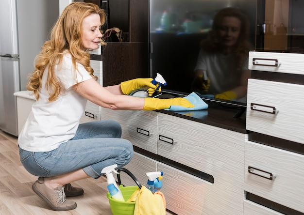 Side view of smiley woman cleaning furniture