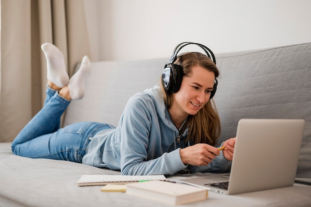 Side view of smiley woman on couch attending on online class