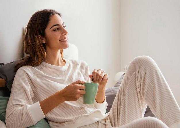 Vista laterale della donna sorridente che mangia caffè a letto