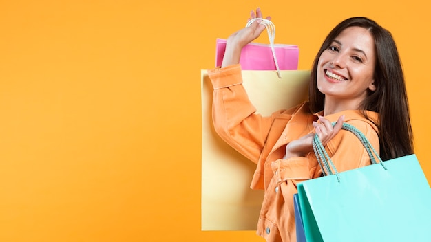 Side view of smiley woman holding up shopping bags