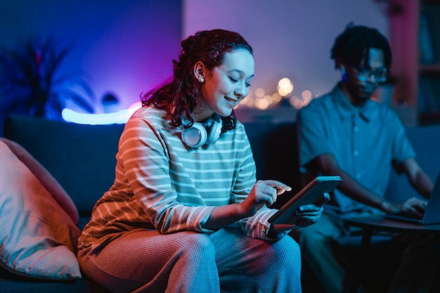 Vista laterale della donna sorridente a casa utilizzando cuffie e tablet