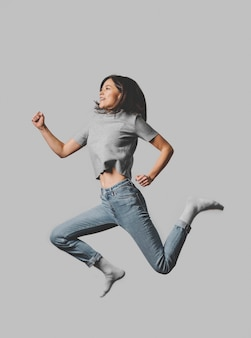 Side view of smiley woman jumping in the air