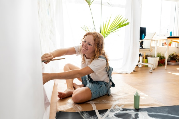 Вид сбоку смайлик женщина рисует на стене