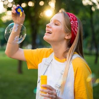 Vista laterale della donna di smiley che gioca con le bolle