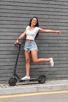 Side view of smiley woman posing with scooter outside