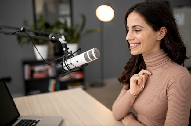 Side view of smiley woman in a radio studio with microphone and laptop