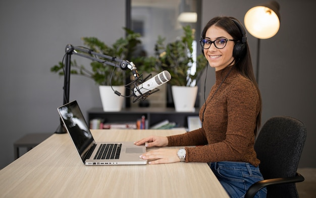 Side view of smiley woman on the radio with microphone and laptop