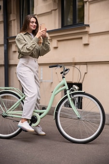 Side view of smiley woman using her smartphone while on the bicycle