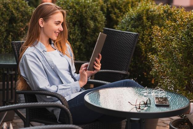Вид сбоку смайлик женщина с помощью планшета