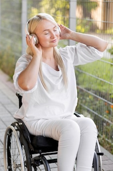 Vista laterale della donna sorridente in sedia a rotelle con le cuffie