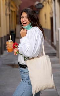 Vista laterale della donna sorridente con maschera facciale e sacchetti della spesa
