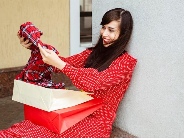 Vista laterale della donna sorridente con borse della spesa e abbigliamento in vendita