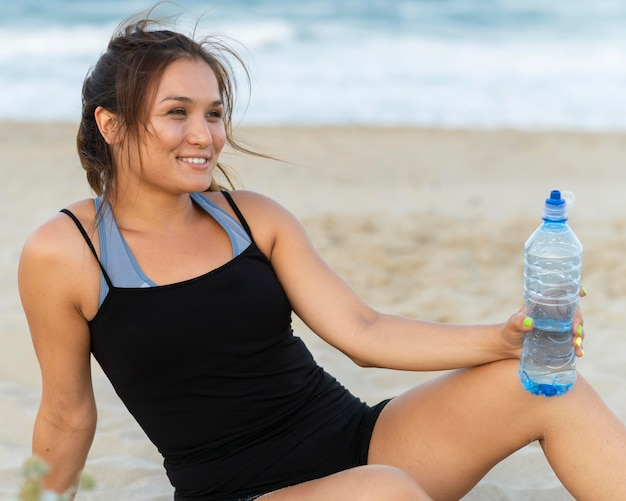 Side view of smiley woman with water bottle on the beach after workout