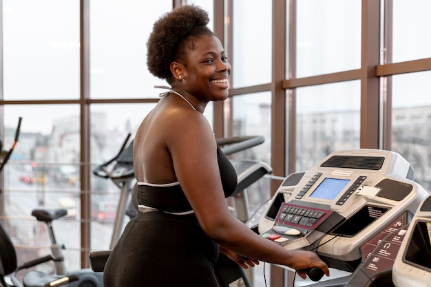 Side view smiley woman working on treadmill