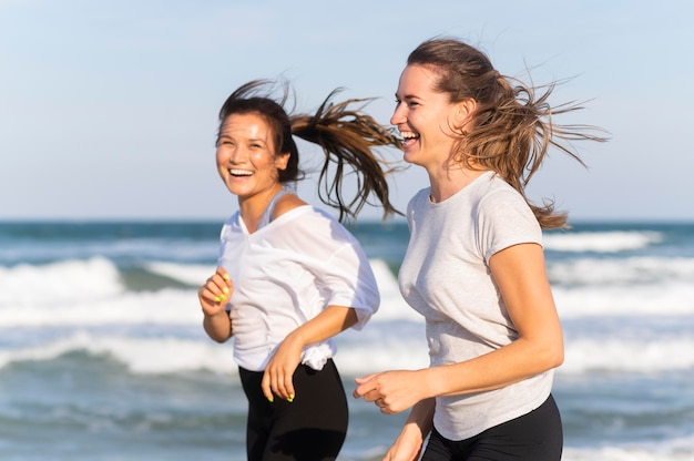 Side view of smiley women running together on the beach