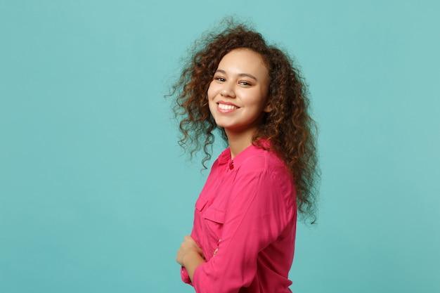 Vista laterale della ragazza africana sorridente in abiti casual rosa che tengono le mani incrociate isolate su sfondo blu turchese parete in studio. persone sincere emozioni, concetto di stile di vita. mock up copia spazio. Foto Gratuite