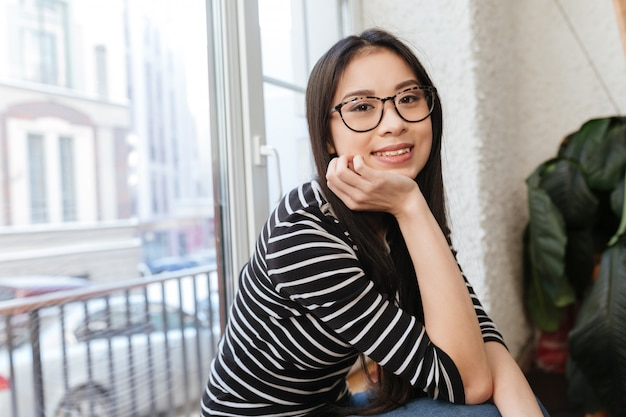 Side view of smiling asian woman sitting on windowsill