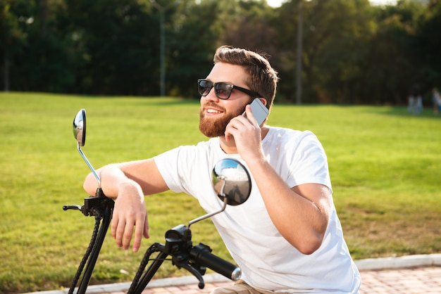 Side view of smiling bearded man in sunglasses sitting on modern motorbike outdoors and talking by the smartphone