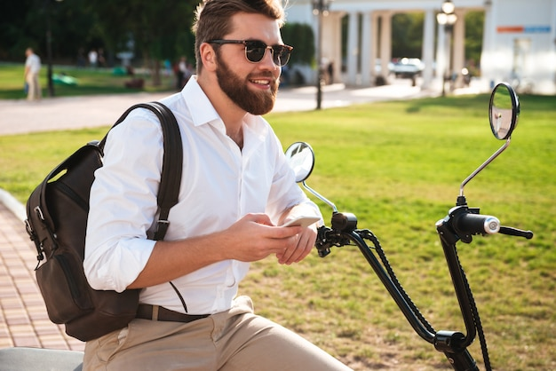 Side view of smiling bearded man in sunglasses sitting on modern motorbike outdoors with smartphone and looking away