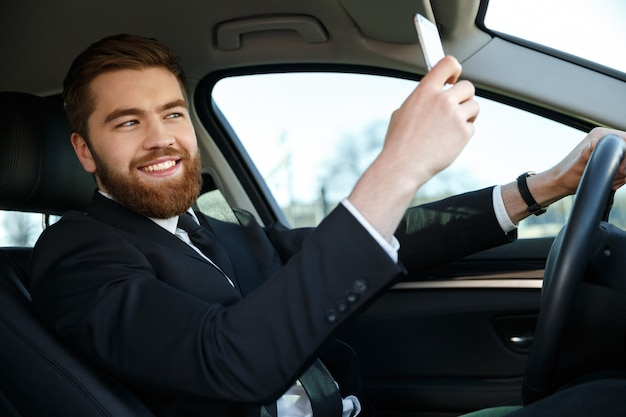 Side view of smiling business man making selfie