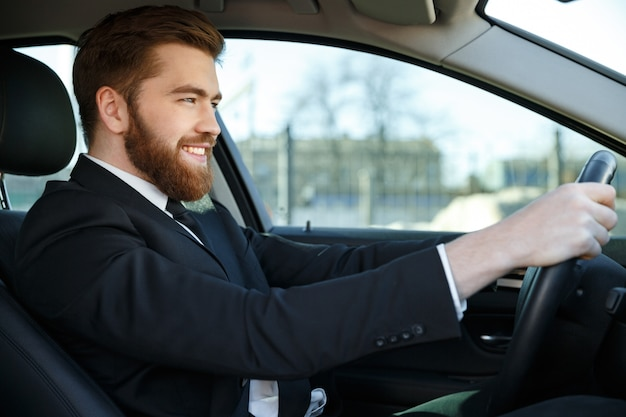 Side view of smiling business man sitting at the wheel