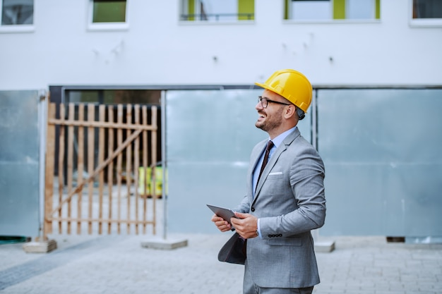 Side view of smiling caucasian elegant architect in suit, with eyeglasses and helmet on head holding tablet and looking up while standing at construction site.