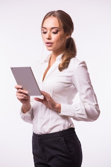 Side view of a smiling confident woman standing and using digital tablet isolated against gray wall