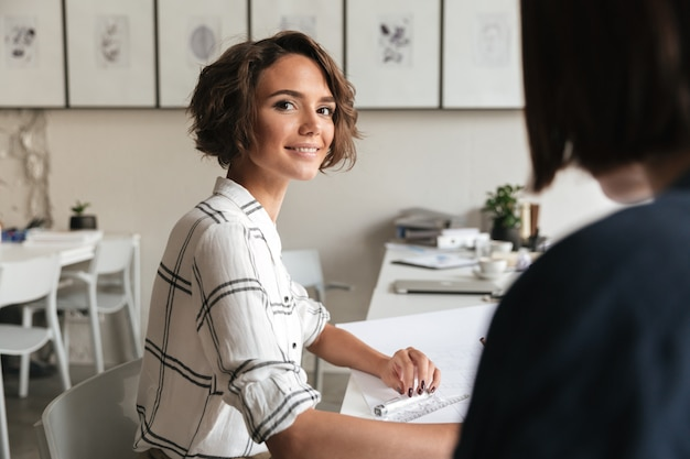 Side view of smiling curly business woman sitting by table