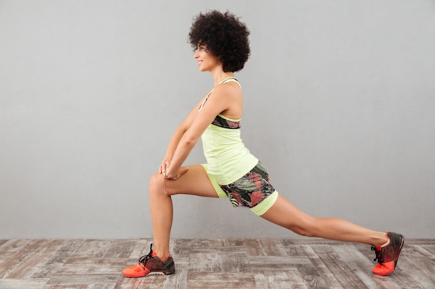 Side view of smiling curly woman stretching