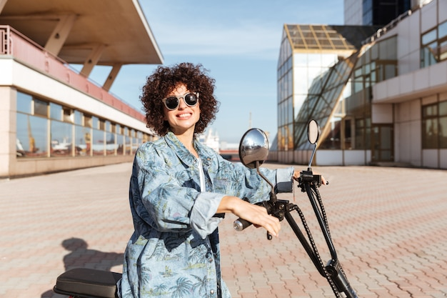 Side view of smiling curly woman in sunglasses posing on modern motorbike outdoors