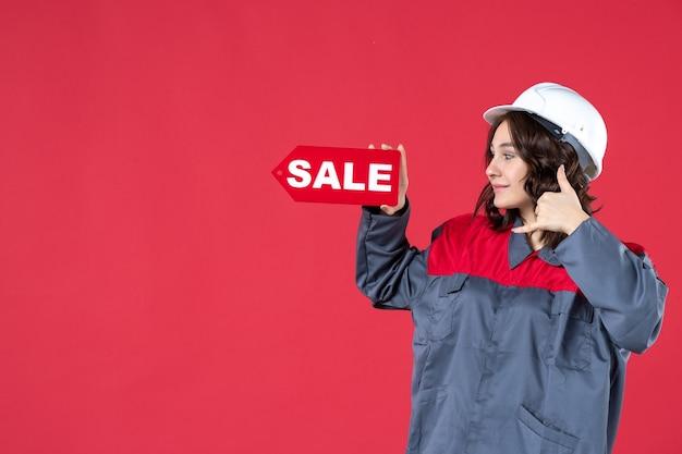 Vista laterale della lavoratrice sorridente in uniforme che indossa elmetto e indicando l'icona di vendita che fa un gesto di chiamata su sfondo rosso isolato