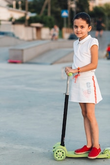 Side view of smiling girl standing on green scooter