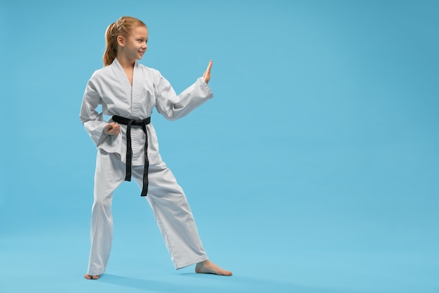 Side view of smiling girl in white kimono training karate