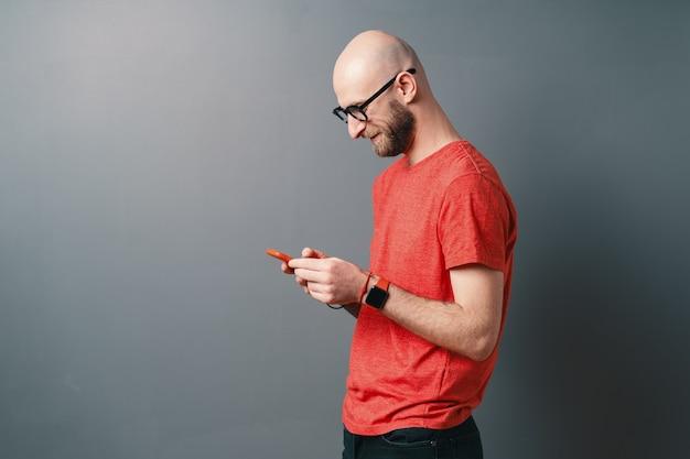 Вид сбоку улыбающийся красивый лысый мужчина с бородой, очками, красной футболкой и текстовыми сообщениями, держащий смартфон